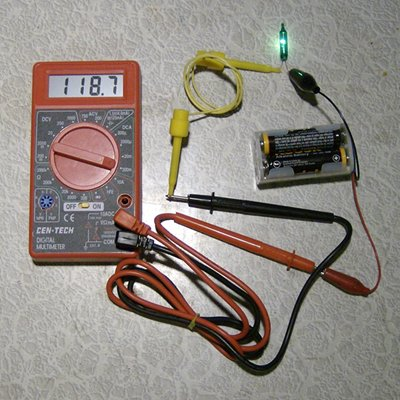 The photo shows a 4 AA cell battery pack which puts out 6 volts, multimeter  set to measure current, and the bulb under test. - How To Test And Identify Bulbs